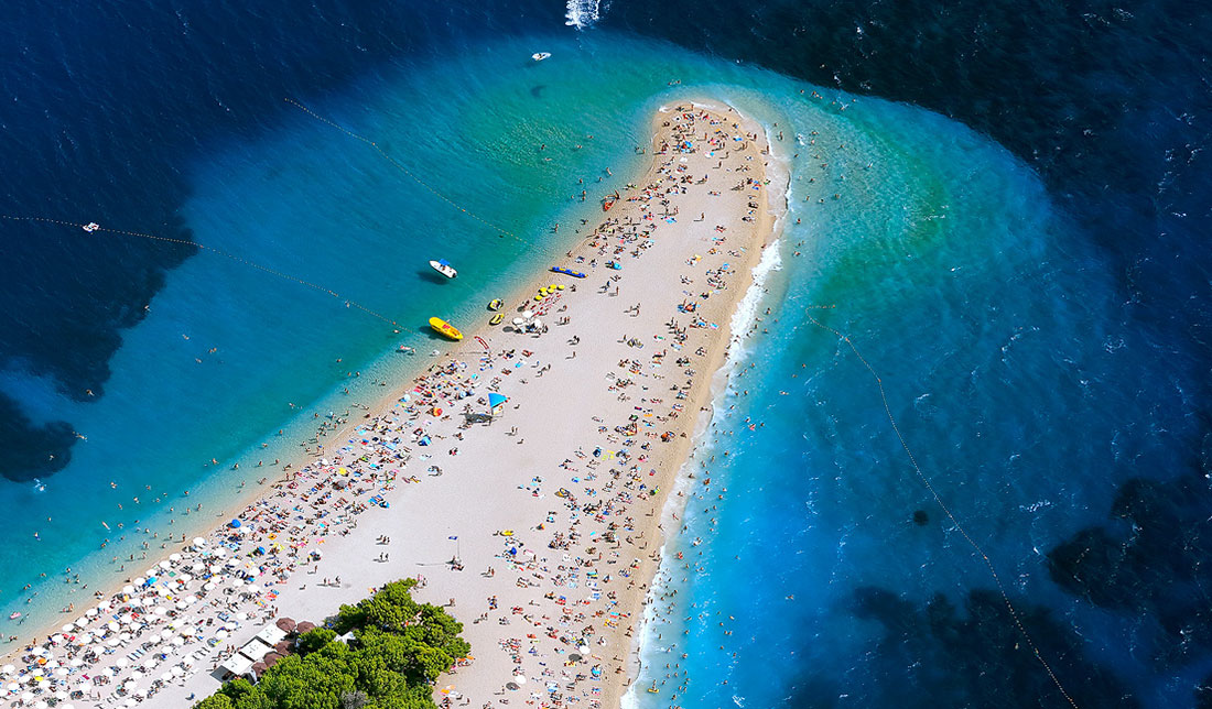 Aerial photo of Zlatni rat beach on island of Brač, pine trees, crystal blue sea and hundred of tourist spread on the beach