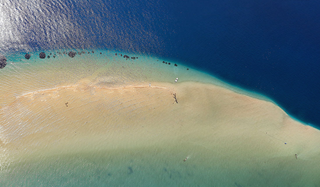 Aerial photo of a sandy beach on the mouth of river Neretva, just yellow sand and deep blue sea