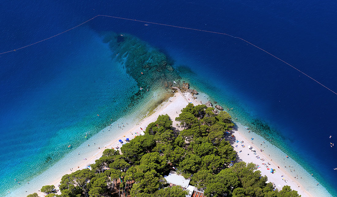 Aerial photo of a Punta rata beach in Brela, with beautiful blue sea and green pine trees