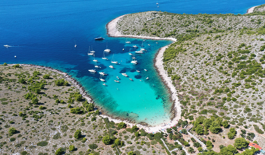 Aerial photo of Lojena beach on Levrnaka, Kornati - white sand, crystal blue sea, boats and green vegetation
