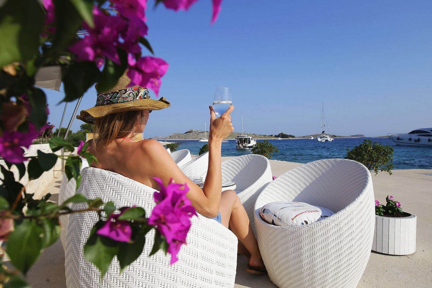 Archipelago Tours Custom Made Tours Exclusive Charter photo of a woman sitting in a lounge chair, holding wine glass and looking at the sea