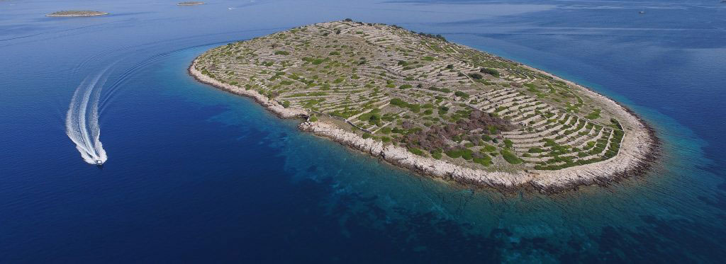 Archipelago Tours Blog and Tips: Islands at your fingertips - island of Bavljenac aerial photo with a boat passing by