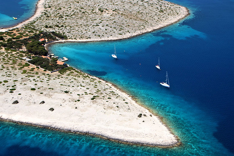 Aerial photo of an island in Kornati with houses, blue sea and yachts