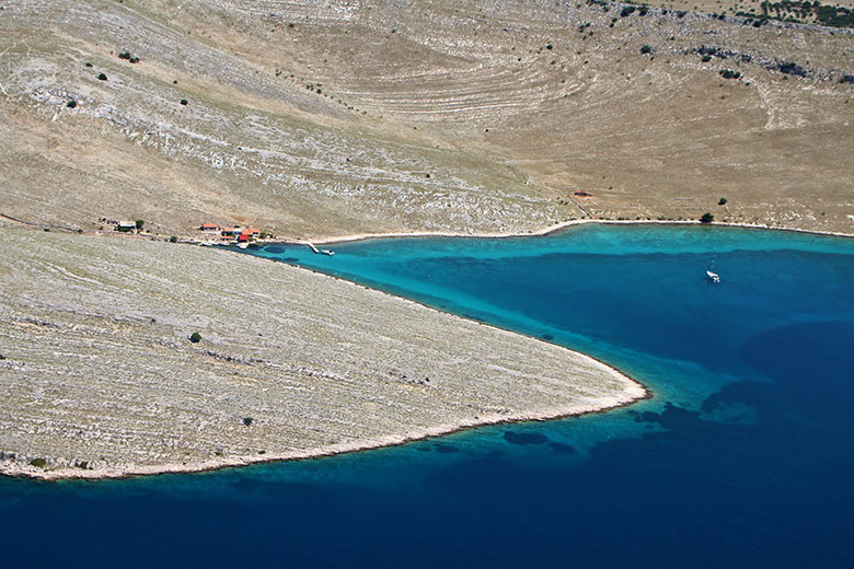 Aerial photo of one of the bays in Kornati with few small houses, few boats, moonlike landscape and clear blue sea