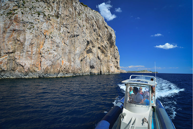 Archipelago Tours boat with tourists on board passing under a cliff in Kornati