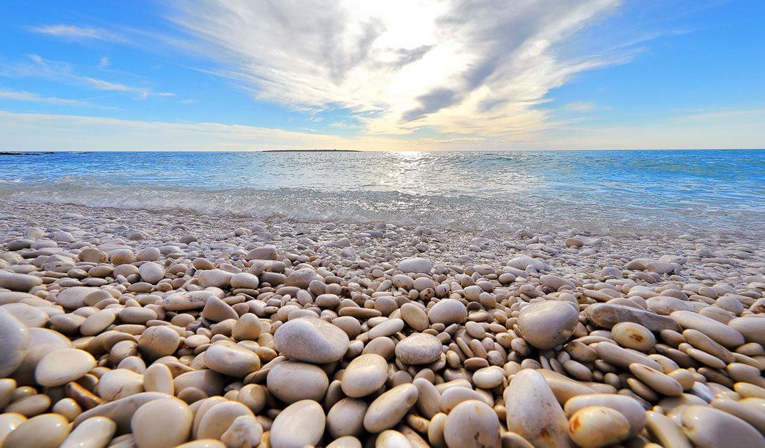Photo of beach pebbles. sea and blue sky