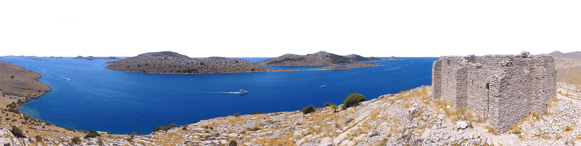 Panoramic photo taken from the air showing Tarac fortress and Kornati islands with boats passing by