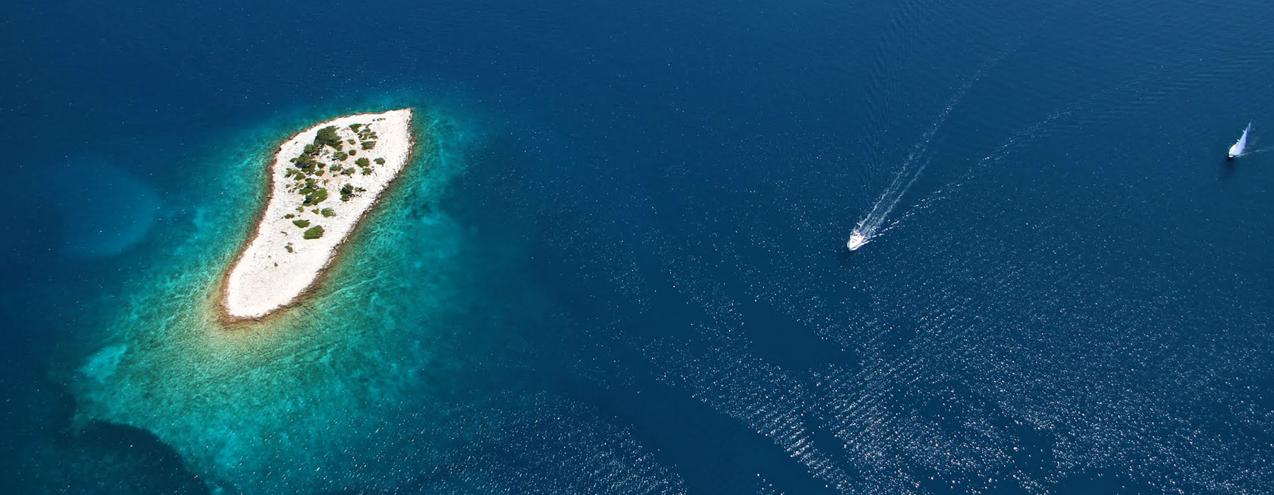 Archipelago Tours Photo ofone small island in Kornati from the air with two boats passing by